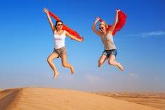 Lyckliga kvinnor som hoppar i öknen Arkivfoton