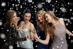 Lyckliga kvinnor som klirrar champagneexponeringsglas över svart Royaltyfri Bild