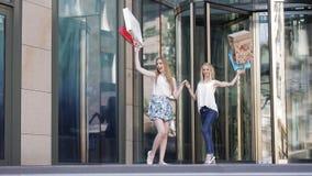 Lyckliga kvinnor som kommer ut ur shoppinggalleria med påsar stock video