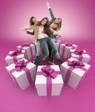 Lyckliga kvinnor som omges av rosa gåvor Fotografering för Bildbyråer