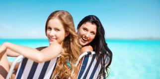 Lyckliga kvinnor som solbadar i stolar över det blåa havet Arkivfoto
