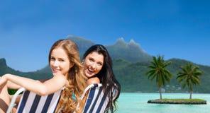 Lyckliga kvinnor som solbadar i stolar på den exotiska stranden Arkivfoto
