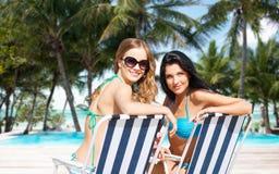 Lyckliga kvinnor som solbadar i stolar på sommarstranden Royaltyfri Bild