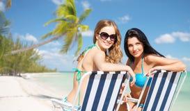 Lyckliga kvinnor som solbadar i stolar på sommarstranden Arkivbilder