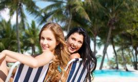 Lyckliga kvinnor som solbadar i stolar på sommarstranden Royaltyfri Fotografi