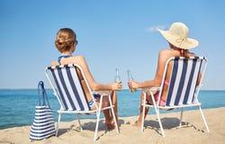 Lyckliga kvinnor som solbadar i vardagsrum på stranden Arkivfoton