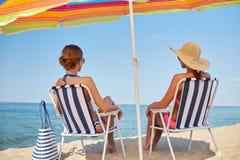 Lyckliga kvinnor som solbadar i vardagsrum på stranden Royaltyfri Fotografi