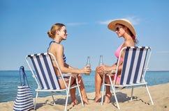 Lyckliga kvinnor som solbadar i vardagsrum på stranden Royaltyfri Bild