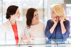 Lyckliga kvinnor som väljer örhängen på smyckenlagret Fotografering för Bildbyråer