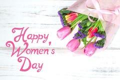 Lyckliga kvinnors dag med buketten av tulpan i bakgrund Arkivfoton