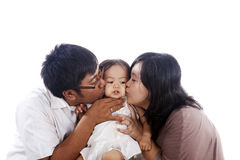 lyckliga kyssande föräldrar för dotter Arkivbilder