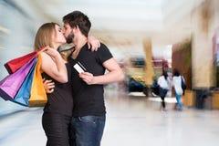 Lyckliga kyssande par med shoppingpåsar på gallerian Royaltyfria Foton