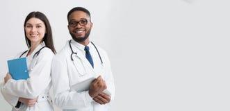 Lyckliga l?karearbetare Stående av två doktorer i vita lag royaltyfri fotografi
