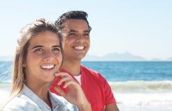 Lyckliga latinska par på stranden Royaltyfri Foto