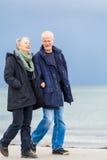 Lyckliga äldre höga par som går på stranden Arkivfoton