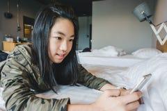 Lyckliga le asiatiska ungar på säng som spelar den smarta telefonen Fotografering för Bildbyråer