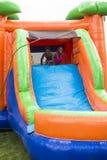 Lyckliga le barn som spelar på ett uppblåsbart glidbanadunshus Arkivfoto