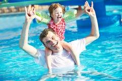 Fader och barn i semesterortsimbassäng Royaltyfri Foto