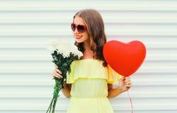 Lyckliga le hållande bukettblommor för kvinna och röd hjärta för luftballong formar över vit Arkivbild