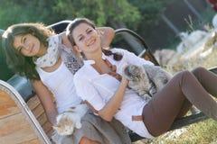 Lyckliga le kvinnor med katten Royaltyfri Bild