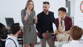 Lyckliga le multietniska startaffärspartners arbetar tillsammans, den unga blonda kvinnan som talar under kontorsmöte lager videofilmer