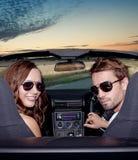 Lyckliga le par i en konvertibel bil. Folk utomhus. Arkivbilder