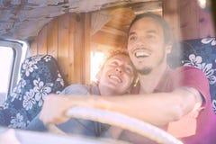 Lyckliga le par inom en tappningminivan - spännande körning för lopp folk för en vägtur med en skåpbilcampare arkivfoto