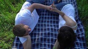 Lyckliga le par som ligger på gräs och att koppla av arkivfilmer