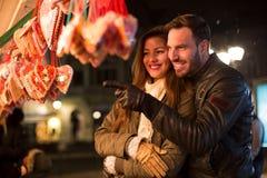 Lyckliga le par som ser sötsakhjärtor på jul, semestrar royaltyfri bild
