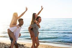 Lyckliga le par som spelar p? stranden arkivfoto