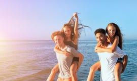 Lyckliga le par som spelar p? stranden fotografering för bildbyråer