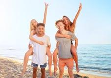 Lyckliga le par som spelar p? stranden royaltyfri fotografi