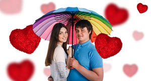 Lyckliga le par under det färgrika paraplyet Arkivfoto