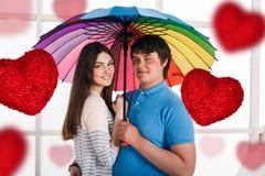 Lyckliga le par under det färgrika paraplyet Royaltyfri Bild