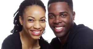 Lyckliga le svarta par som ser kameran på vit bakgrund Arkivfoton