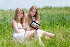 Lyckliga le tonåriga flickor och minnestavladator Arkivfoto