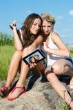 Lyckliga le tonåriga flickor och minnestavladator utomhus Arkivbilder