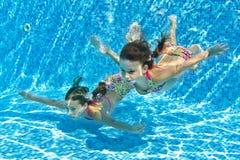 Lyckliga le undervattens- barn i simbassäng Arkivbilder