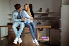 Lyckliga le unga par i den blåa grov bomullstvilltorkduken som sitter i köket royaltyfri fotografi