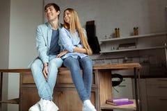 Lyckliga le unga par i den blåa grov bomullstvilltorkduken som sitter i köket royaltyfri bild