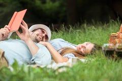 Lyckliga le unga par som kopplar av i, parkerar Ligga på en picknickfilt royaltyfri foto
