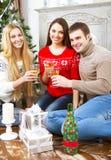 Lyckliga le vänner som dricker champagne vid det Cristmas trädet Royaltyfri Foto