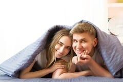 Lyckliga leendepar under filten i morgonen i sovrum royaltyfri fotografi
