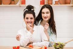 Lyckliga lesbiska par som förbereder mat i kök royaltyfria bilder