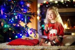 Lyckliga lilla flickan som den har, mjölkar och kakor vid en spis i en hemtrevlig mörk vardagsrum på julhelgdagsafton arkivfoton
