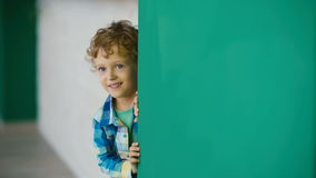 Lyckliga Little Boy kikar från väggen och le lager videofilmer