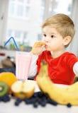 Lyckliga Little Boy som dricker en sund Smoothie i hans hemtrevliga hem, w royaltyfria bilder