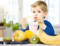 Lyckliga Little Boy som dricker en sund Smoothie i hans hemtrevliga hem, w arkivfoton