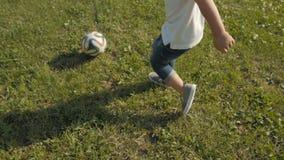 Lyckliga Little Boy som spelar med bollen i trädgården Liten unge som spelar Soceer utomhus arkivfilmer