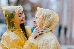 Lyckliga ?lska par, grabben och hans ikl?dda gula regnrockar f?r flickv?n kramar p? gatan i regnet royaltyfria foton